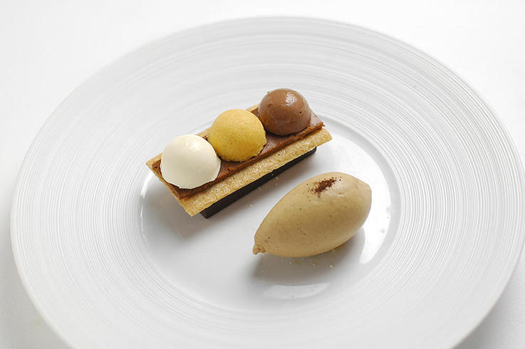 Caramelized pears in a chocolate case with chocolate and hazelnut mousses and chicory ice cream